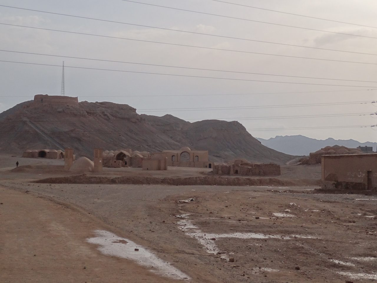 Dakhma with old-looking buildings in the foreground